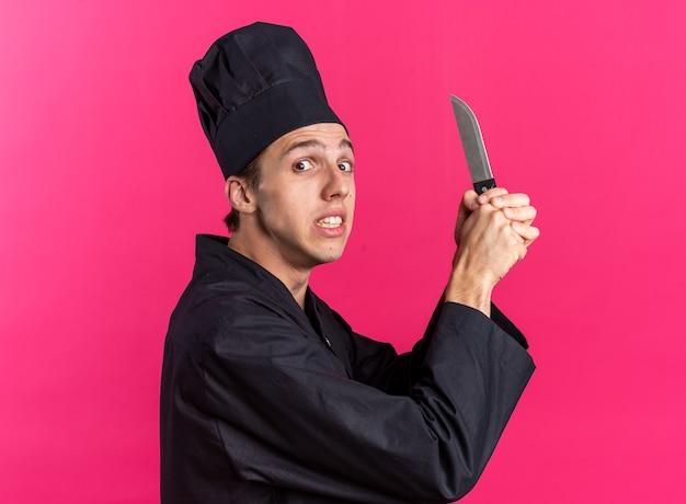 Spaventato giovane maschio biondo cuoco in uniforme da chef e berretto in piedi in vista di profilo tenendo il coltello con entrambe le mani guardando la telecamera isolata sulla parete rosa