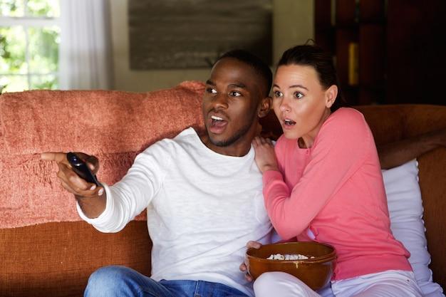 Giovani coppie spaventate che guardano tv
