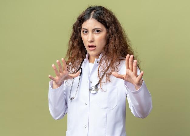 Giovane dottoressa spaventata che indossa abito medico e stetoscopio facendo gesto di rifiuto isolato su parete verde oliva