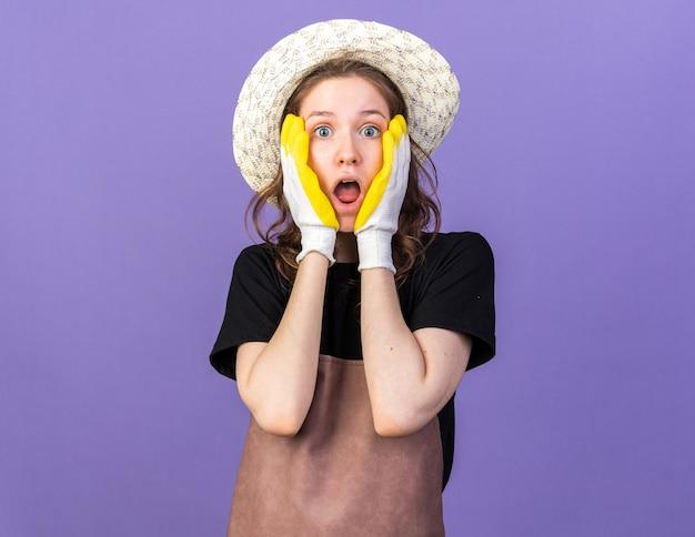 Una giovane giardiniera spaventata che indossa un cappello da giardinaggio con guanti ha coperto il viso con le mani isolate sul muro blu