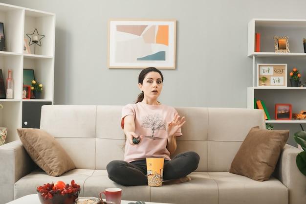 Ragazza spaventata che tiene fuori il telecomando della tv, seduta sul divano dietro il tavolino da caffè nel soggiorno