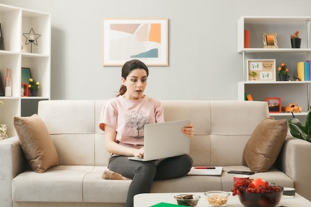 Ragazza spaventata con laptop seduto sul divano dietro il tavolino nel soggiorno