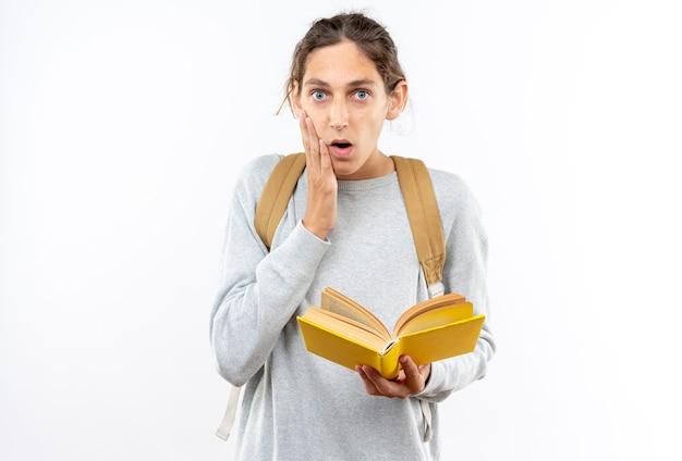 Giovane studente spaventato che indossa uno zaino con in mano un libro che mette la mano sulla guancia isolata sul muro bianco