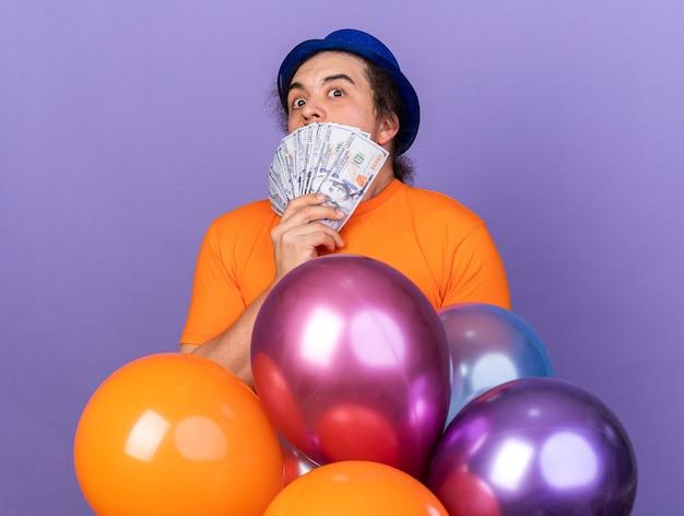 Giovane spaventato che indossa un cappello da festa in piedi dietro i palloncini ha coperto il viso con contanti isolati sul muro viola