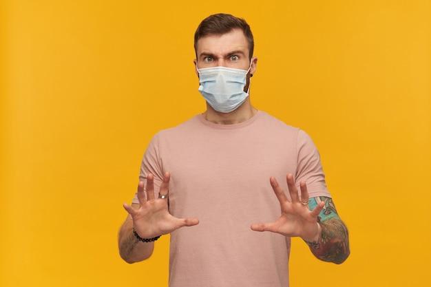 Spaventato giovane uomo barbuto tatuato in maglietta rosa e maschera igienica per prevenire l'infezione con le mani davanti a sé e difendersi dalla minaccia sul muro giallo