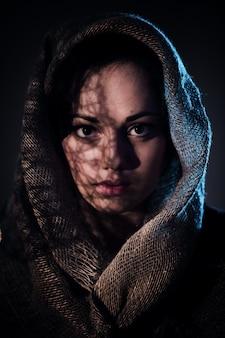 Giovane donna spaventata che copre il viso con sciarpa afgana