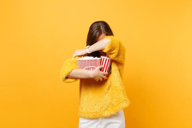 Giovane donna spaventata con la testa più bassa in occhiali 3d imax che guardano film che nascondono il viso coprente con braccio tenere una tazza di popcorn di soda cola isolata su sfondo giallo. persone sincere emozioni nel cinema.