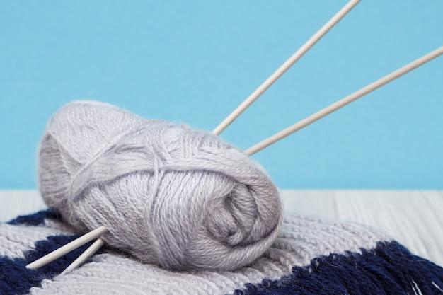 Sciarpa e matassa di filo con ferri da maglia in metallo su tavole grigie e sfondo blu. concetto di maglieria.