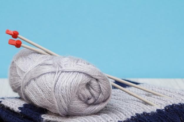 Sciarpa e matasse di filo con ferri da maglia in metallo su tavole grigie e sfondo blu. concetto di maglieria.