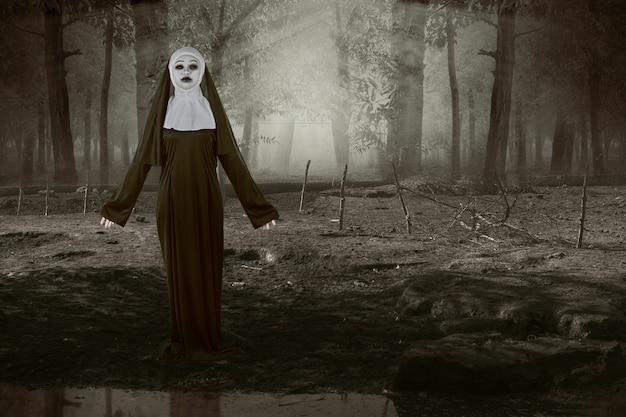 Suora diavolo spaventoso in piedi sulla foresta infestata