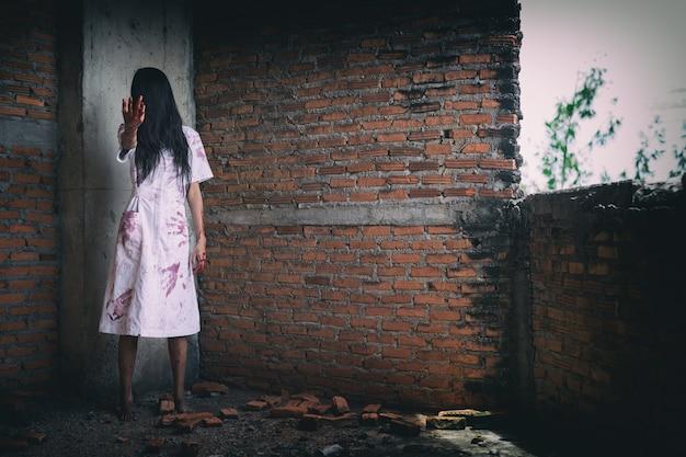 La donna fantasma spaventosa oscura nella casa stregata il tema di halloween raggiunge e sangue