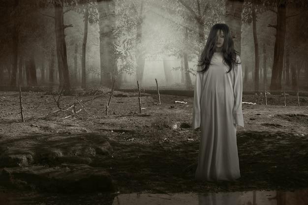 Donna fantasma spaventosa in piedi con la foresta infestata