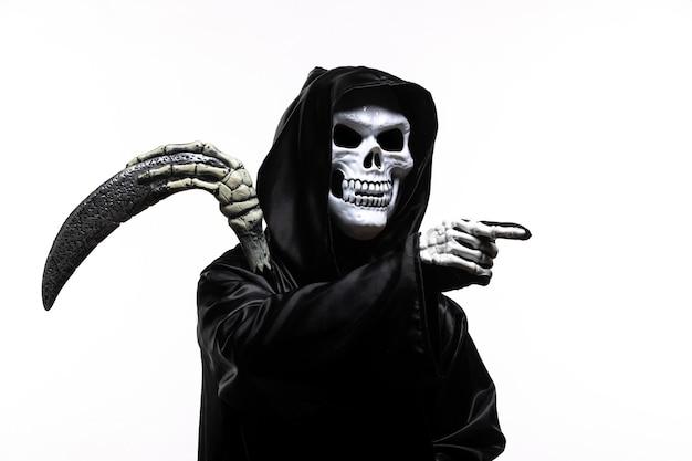 Mietitore spaventoso in abiti neri con la falce che indica su bianco