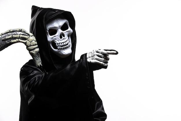 Mietitore spaventoso in abiti neri con falce su bianco