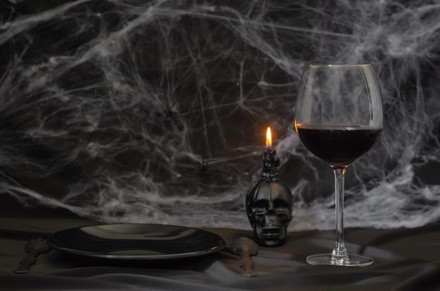 Concetto spaventoso della cena di halloween con un bicchiere di vino rosso, piatto nero, coltello, forchetta e candela teschio con ragnatela su sfondo nero.