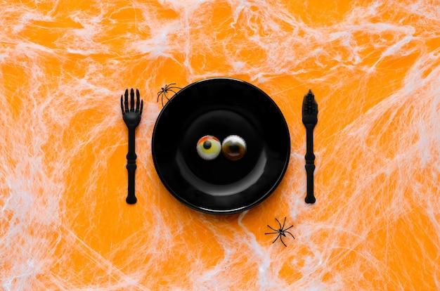 Concetto spaventoso della cena di halloween con bulbi oculari di gelatina su banda nera, coltello e forchetta con ragno e ragnatela su sfondo arancione.