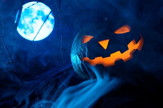 Zucca spaventosa di halloween con la faccia luminosa con la luna piena nella nebbia