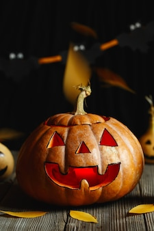 Spaventosa testa di zucca con fiamma e alcune piccole zucche dipinte. faccia di halloween, dolcetto o scherzetto.