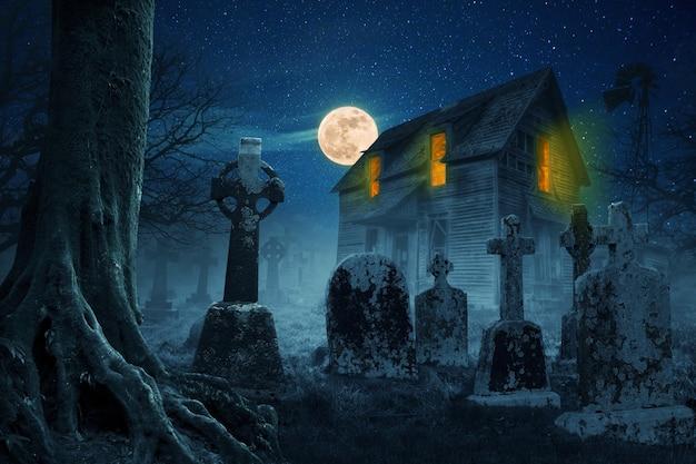 Casa spaventosa nella foresta vicino al cimitero di notte con la luna piena e le stelle. concetto di idea di halloween