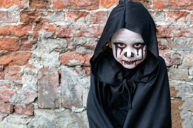 La bambina spaventosa in un piccolo costume da zombie guarda spaventosamente la telecamera contro un muro di mattoni.