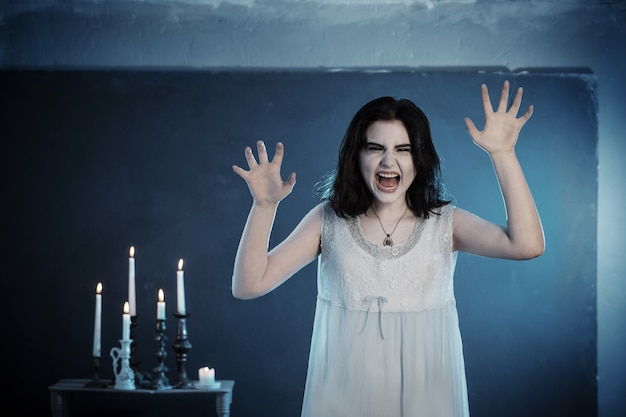 Ritratto spaventoso di giovane ragazza del vampiro sulla superficie blu