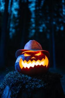 Zucca spaventosa con una faccia scolpita su un ceppo in una cupa foresta concetto vacanza di halloween