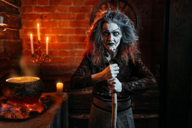 Strega spaventosa sulla seduta spirituale, cucina, stregoneria con candele. l'indovina femminile chiama gli spiriti, terribile futuro cassiere