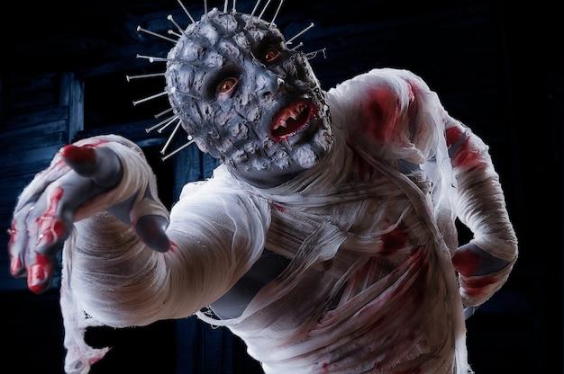 Zombie spaventoso in costume da festa di festa di halloween con bende e sangue Foto Premium