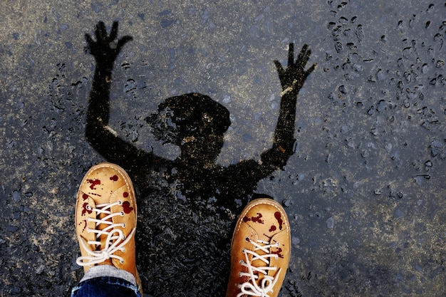 Scary zombie man with dropped blood on shoes sollevare la mano creepy per halloween