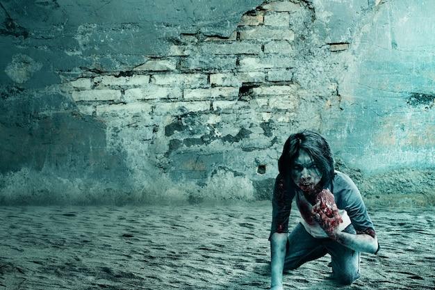 Zombie spaventoso con sangue e ferita sul corpo mangia la carne cruda con il muro rotto