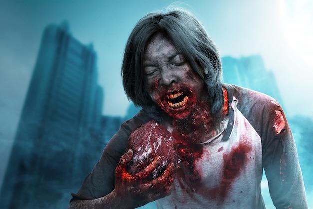 Lo zombi spaventoso con sangue e ferita sul suo corpo mangia la carne cruda