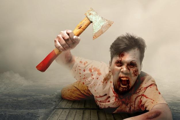 Zombie spaventoso con sangue e ferita sul suo corpo che tiene un'ascia che striscia con sfondo nebbioso