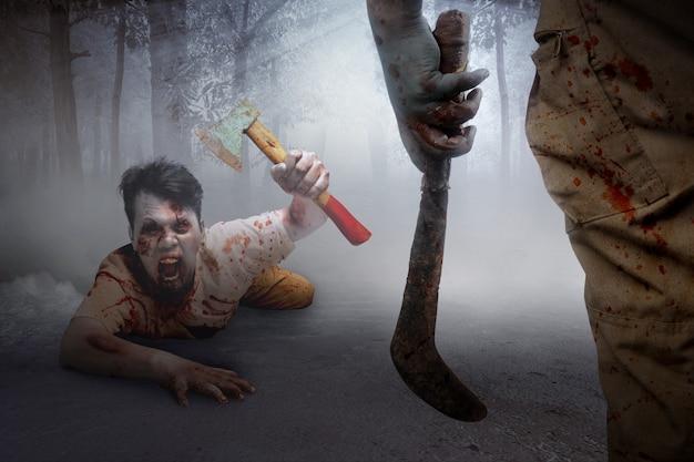 Zombie spaventoso con sangue e ferita sul suo corpo che tiene l'ascia che striscia con lo sfondo della foresta infestata