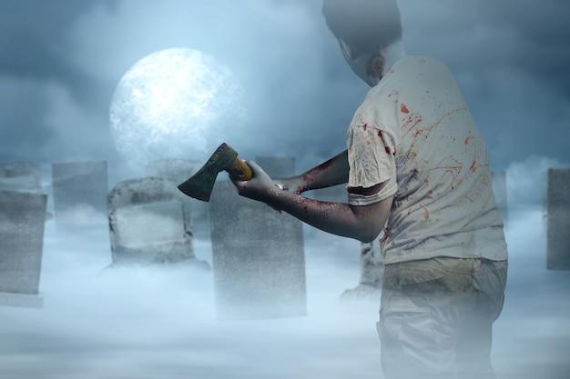 Zombie spaventoso con sangue e ferita sul suo corpo che tiene l'ascia in piedi con lo sfondo della scena notturna