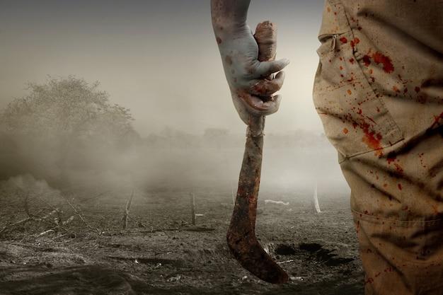 Zombie spaventoso con sangue e ferita sul corpo che tiene la falce in piedi sul campo