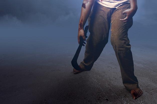 Zombie spaventoso con sangue e ferita sul suo corpo che tiene la falce che cammina sul campo