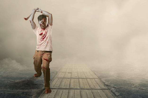 Zombie spaventoso con sangue e ferita sul suo corpo che tiene la falce che cammina sul sentiero