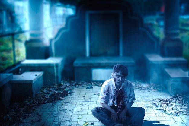 Zombie spaventoso con sangue e ferita sul corpo seduto al cimitero