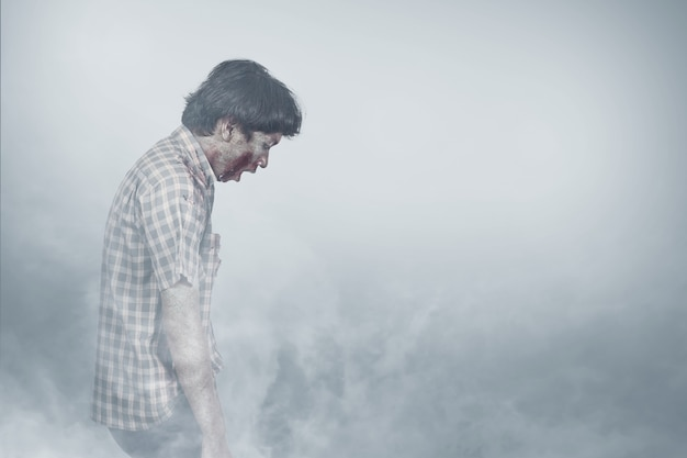 Zombie spaventoso con sangue e ferita sul suo corpo in piedi nella nebbia