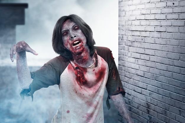 Zombie spaventoso con sangue e ferita sul suo corpo che cammina nell'edificio abbandonato