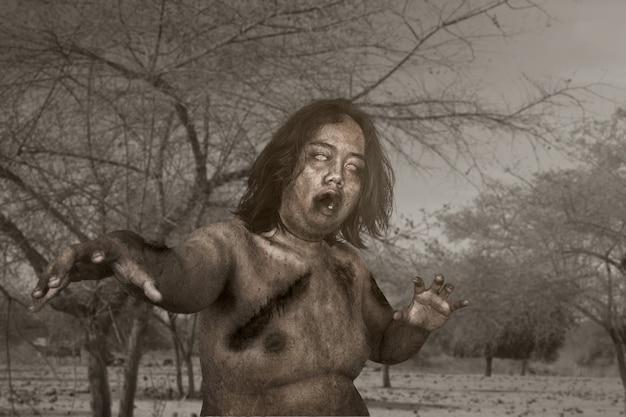Zombie spaventoso con sangue e ferita sul suo corpo che cammina sul campo