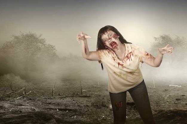 Zombie spaventoso con sangue e ferita sul corpo che cammina sul campo