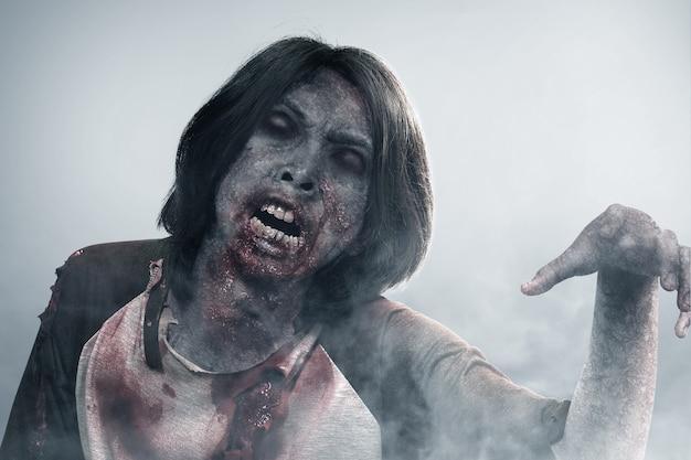 Zombie spaventoso con sangue e ferita sul suo corpo che cammina nella nebbia