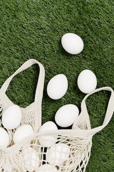 Borsa sparsa con uova bianche sulla vista dall'alto di pasqua vacanza prato