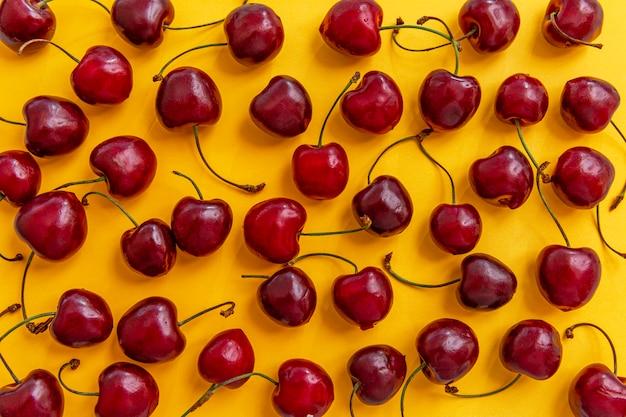 Bacche sparse di ciliegie mature su uno sfondo giallo brillante. vista dall'alto. vitamine stagionali.