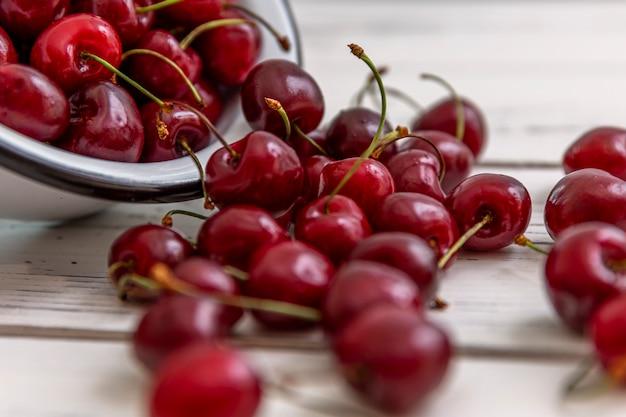 Bacche sparse di ciliegie mature su uno sfondo in legno chiaro e in una ciotola. vista dall'alto. vitamine stagionali.