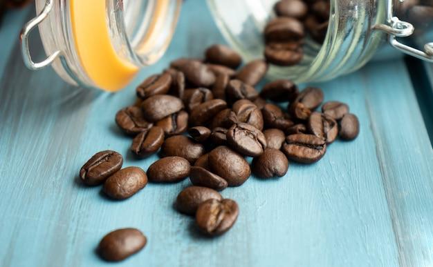 Chicchi di caffè sparsi da un barattolo di vetro su uno sfondo nero. umore del caffè.