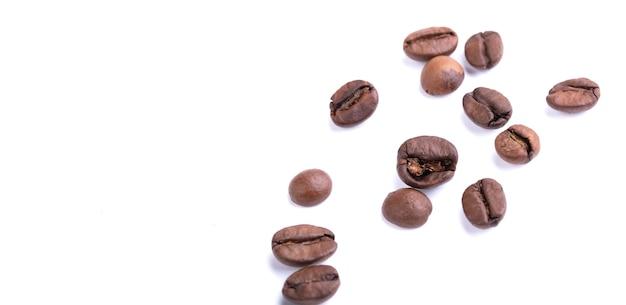 Chicchi di caffè sparsi su uno sfondo bianco. arabica o robusta.