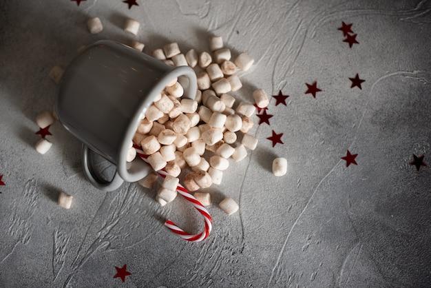 Sparse da un piccolo secchio di marshmallow su uno sfondo bianco.