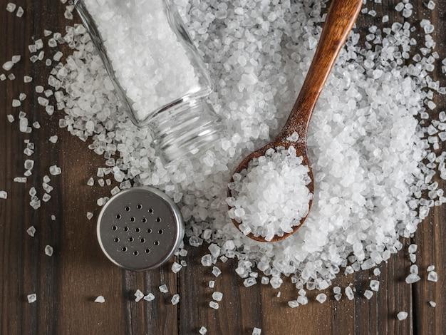 Sparse grande sale marino con un cucchiaio di legno e una saliera. sale marino macinato a pietra.